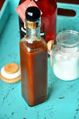 Bandeja azul brillante con bourbon, azúcar y una botella de salsa de caramelo de borbón casera