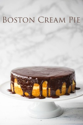 El tradicional Boston Cream Pie en un soporte para pasteles con bizcocho, pudín de vainilla y glaseado de chocolate oscuro.