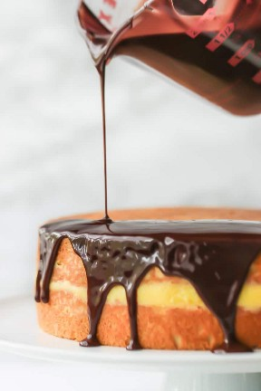 La cobertura de chocolate se vertió sobre una esponja de vainilla rellena con crema pastelera para hacer el clásico Boston Cream Pie.