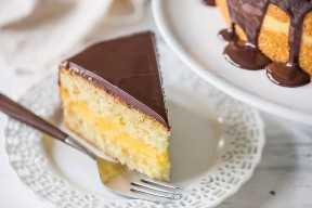 Rebanada perfecta de Boston Cream Pie en un plato al lado de la tarta llena, que muestra la cobertura de ganache que gotea por los lados.