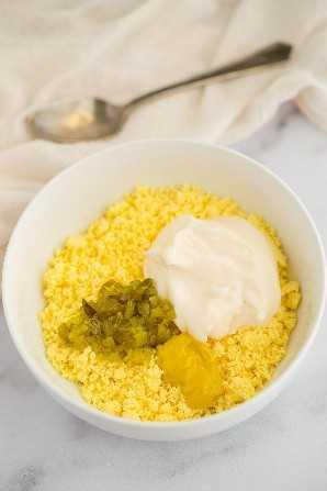 Un tazón blanco lleno de yemas de huevo desmenuzadas, mayonesa, mostaza y condimento.