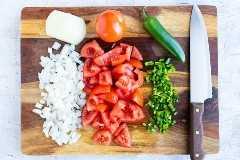 Cebolla picada, tomates frescos y jalapeños que se pican en una tabla de cortar de madera.