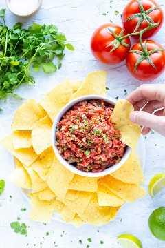 Una mano sumergiendo una tortilla en un tazón lleno de salsa de tomate estilo restaurante con tomates frescos y cilantro al lado.