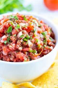 Un primer plano de salsa de salsa mexicana con tomates frescos, cilantro, cebolla y jalapeños.