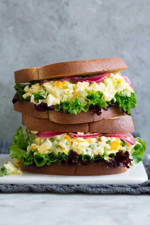 Pilha de dois sanduíches da salada do ovo em uma bandeja branca do serviço que senta-se no mármore com um fundo cinzento.
