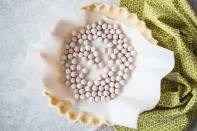 Corteza de pastel para hornear a ciegas con pergamino y pesos de pastel de cerámica.