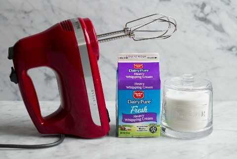 Azúcar crema batida y una batidora eléctrica manual sobre una superficie de mármol