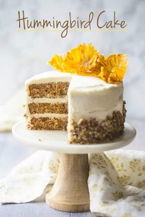 Pastel de colibrí clásico sobre pedestal de pastel de mármol, decorado con flores de piña.