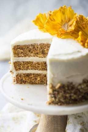 Primer plano de la torta de colibrí del sur con glaseado de queso crema, nueces y flores de piña.