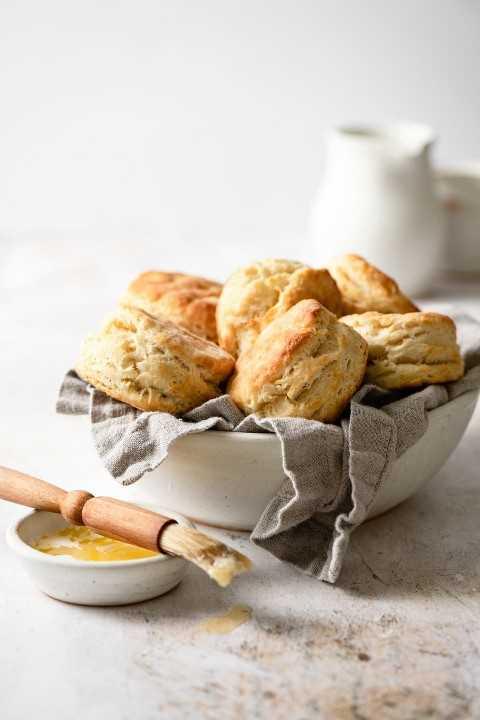 Tazón de fuente lleno de galletas de mantequilla con un pincel de pastelería y mantequilla en el lado.