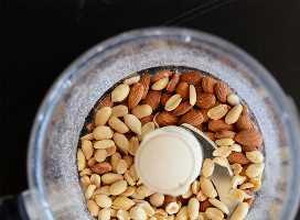 Procesador de alimentos relleno de cacahuetes y almendras para hacer galletas sin hornear