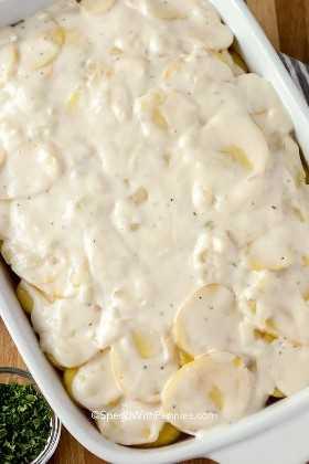 Patatas festoneadas en capas y preparadas antes de hornear en el horno