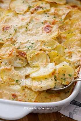 Sirve patatas cremosas festoneadas con perejil en una fuente para hornear.