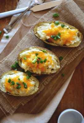 Tabla para cortar con papas al horno con coliflor y queso cheddar con cebolla verde