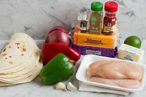 Los ingredientes de la quesadilla que se muestran aquí incluyen tortillas, mantequilla, queso, pollo, pimientos, cebolla roja, ajo, comino, chile en polvo y limón.