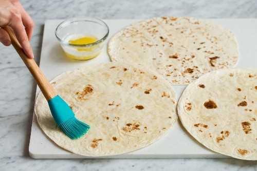 Cepillar las tortillas con mantequilla derretida para hacer quesadillas.