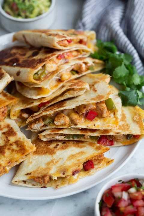 Quesadillas en un plato servido con guacamole y salsa.