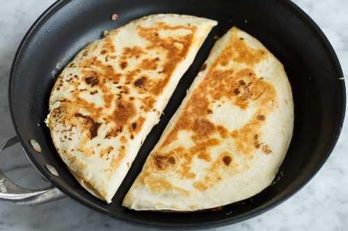 Dos quesadillas en una sartén que se muestra después de cocinar con exterior marrón dorado.