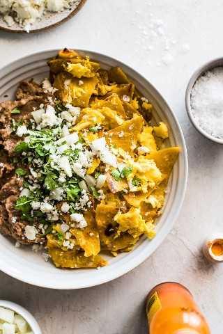 Migalhas feitas de tortilhas de milho crocantes e ovos mexidos em uma tigela com feijão frito.