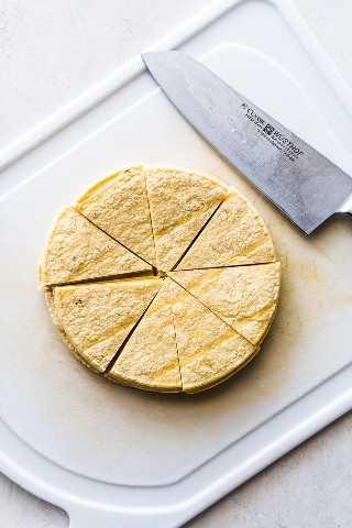 Corte as tortilhas de milho em uma tábua branca, preparando-se para se transformar em migalhas.