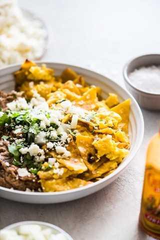 Receita de migalhas feita com tortilhas de milho frito e ovos em uma tigela com feijão frito coberto com queijo fresco.