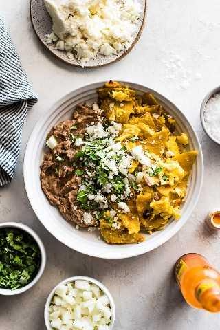 Uma tigela branca cheia de migalhas e feijão frito com coentro, cebola e queijo fresco.