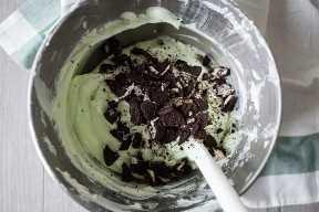 Pastel de saltamontes relleno con oreos machacados en un bol de mezcla de acero inoxidable.