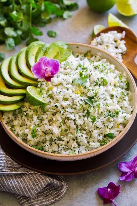 Sirviendo un tazón lleno de cilantro con arroz de limón adornado con rebanadas de aguacate, hojas de cilantro, flor de orquídea y limón.