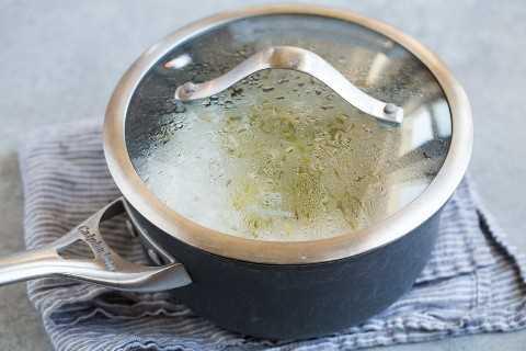 Descansando arroz de cilantro y cal en una cacerola cubierta con una tapa de calor en una servilleta gris.