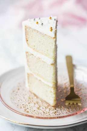 Rebanada alta de pastel blanco con crema agria, en un plato rosado con un tenedor de oro.