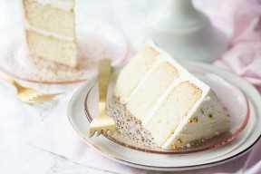 Duas fatias de bolo de casamento branco nas placas cor de rosa com garfos de ouro.