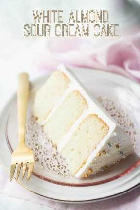 """Fatia de bolo de creme de amêndoa branca deitada de lado, em um prato rosa com uma sobreposição de texto que diz """"Bolo de creme de leite de amêndoa branca""""."""