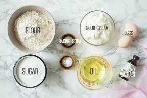 Ingredientes para hacer la torta blanca de la crema agria de la almendra en un fondo de mármol.