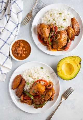 Pollo Guisado con Pollo Estofado Dominicano servido en un plato con arroz blanco, frijoles y maduros