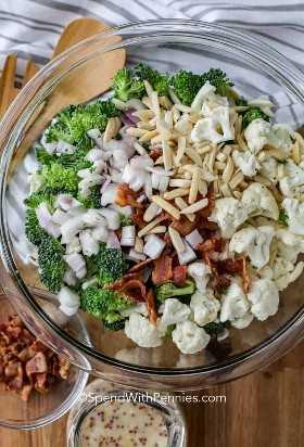 Ingredientes de la ensalada de coliflor y brócoli en un tazón para mezclar claro con aderezo y tocino al lado.