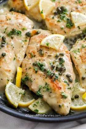 Salsa de pollo piccata vertida sobre el pollo buscado con limón y alcaparras