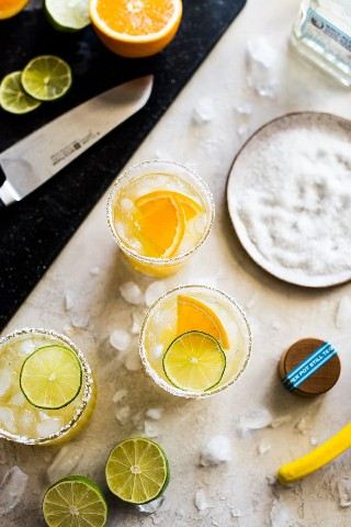 Margaritas flacas en una mesa con sal, limas, tequila, naranjas y cubitos de hielo.