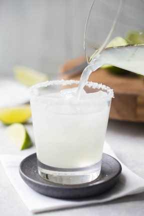 Verter el cóctel de margarita sobre hielo en un vaso bajo con un borde salado.