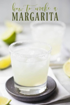 """Dos margaritas en vasos de rocas con bordes salados y una superposición de texto que dice """"Cómo hacer una Margarita""""."""