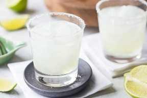 Dos cócteles de margarita sobre hielo con bordes salados y gajos de lima al fondo.
