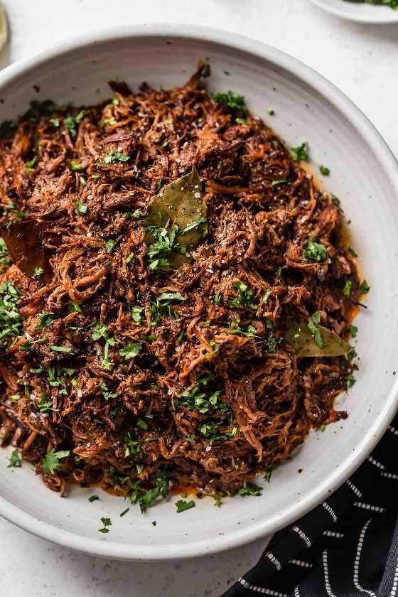 Olla de cocción lenta, rallado, carne de res en un tazón blanco para servir, adornado con cilantro.