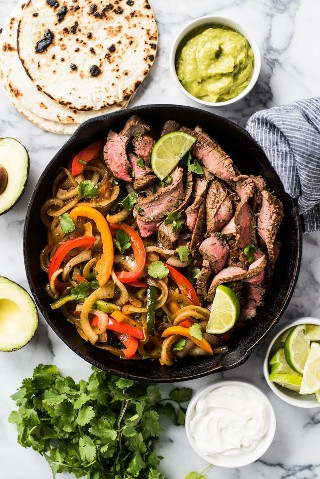 Fajitas de carne cocinadas con cebolla y pimientos en una sartén de hierro fundido negro