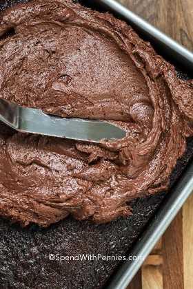Difundir glaseado de crema de chocolate sobre un pastel de chocolate