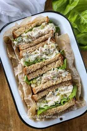 Un plato de servir lleno de sándwiches de ensalada de atún envueltos en papel pergamino con lechuga.