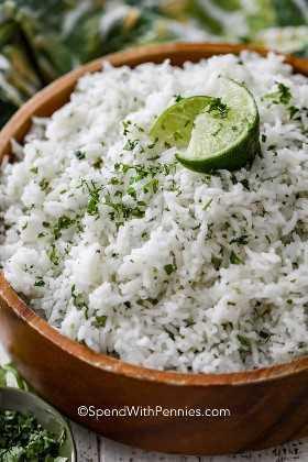 Un cuenco de madera de cilantro de arroz con cilantro picado y rodajas de limón.