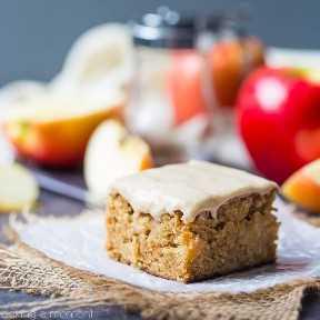 Arce Iced Apple Blondie en una servilleta con manzanas en el fondo