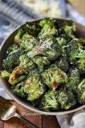 Brócoli asado en un tazón de fuente de traste cubierto con queso parmesano.