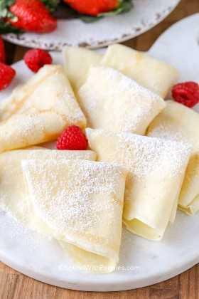 Crepes doblados espolvoreados con azúcar glas y frambuesas en un plato de servir.