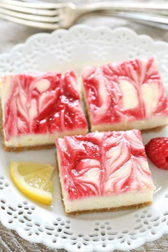 Estas barras de cheesecake de limón y frambuesa cuentan con un suave y cremoso cheesecake de limón que se rellena con un remolino de frambuesa sobre una base de galletas caseras.