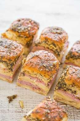 Deslizadores de jamón y queso: jamón jugoso horneado y suizo, acurrucados en suaves rollos hawaianos y cepillados con un manteca de Dijon, cebolla y semillas de amapola. ¡Rápido, FÁCIL y una fiesta FAVORITA!